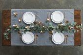 Fotografia vista superiore di impostazione tabella rustica con eucalipto, appannata posate, bicchieri da vino, candele e piatti vuoti sul tavolo