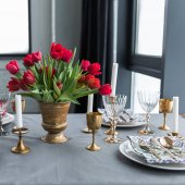 Fotografie close up view of bouquet of red tulips on tabletop with arranged vintage cutlery and candles