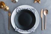 Fotografie pohled shora černé prázdný talíř, ubrousek a staré staromódní zašlé příbory na stůl