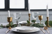 Photo close up view of rustic table setting with wine glasses, eucalyptus, vintage cutlery, candles in candle holders and empty plates