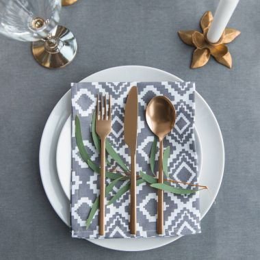 flat lay with old fashioned cutlery, napkin, green plant on plates on tabletop