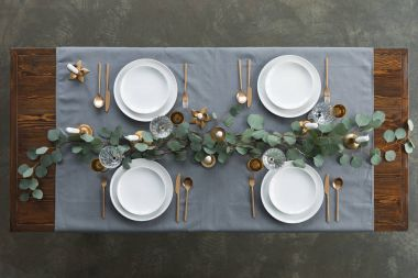 top view of rustic table setting with eucalyptus, tarnished cutlery, wine glasses, candles and empty plates on tabletop