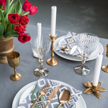 close up view of rustic table arrangement with red tulips, empty wine glasses, vintage silverware and plates