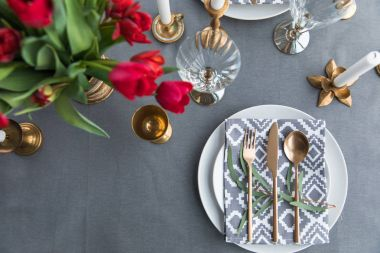 top view of rustic table setting with bouquet of red tulips and arranged old fashioned silverware