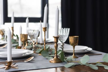 rustic table arrangement with eucalyptus, vintage cutlery, candles in candle holders and empty plates