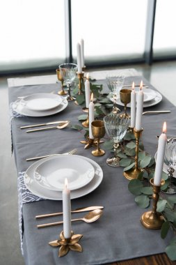 close up view of rustic table arrangement with eucalyptus, vintage cutlery, candles in candle holders and empty plates