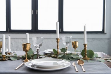 close up view of rustic table arrangement with eucalyptus, tarnished cutlery, candles in candle holders and empty plates