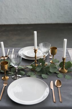 close up view of rustic table setting with eucalyptus, old fashioned tarnished cutlery, candles in candle holders and empty plates