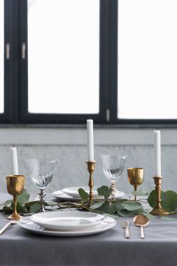 close up view of rustic table setting with eucalyptus, vintage tarnished cutlery, candles in candle holders and empty plates