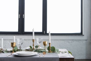 close up view of rustic table arrangement with eucalyptus, vintage tarnished cutlery, candles in candle holders and empty plates