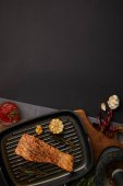 Fotografie top view of arranged grilled salmon steak on wooden cutting board, ingredients and sauce on black tabletop