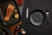 top view of arranged grilled salmon steak on wooden cutting board, sauce and cutlery on black tabletop