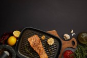 top view of arranged grilled salmon steak on wooden cutting board, sauce, ingredients and cutlery on black tabletop