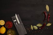 Fotografie flat lay with cutlery, sauce, chili peppers, spices and lemon pieces on black tabletop