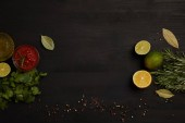 Fotografie flat lay with sauce, citrus fruits pieces, spices, parsley and rosemary on black surface