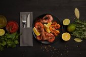 Fotografie flat lay with grilled shrimps with lemon pieces on plate and arranged sauce, spices, ingredients and cutlery around on black surface