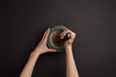 partial view of woman with mortar and pestle on black surface