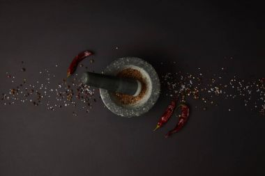 flat lay with mortar, pestle, spices and chili peppers on black tabletop