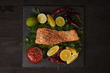 top view of grilled salmon steak, pieces of lime and lemon, chili peppers and sauce on black surface