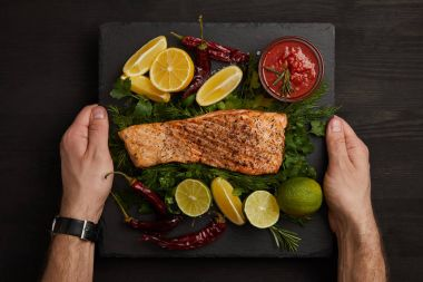 partial view of male hands, grilled salmon steak, sauce and arranged citrus fruits on black surface