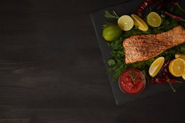 top view of grilled salmon steak, pieces of lime and lemon and sauce on black surface