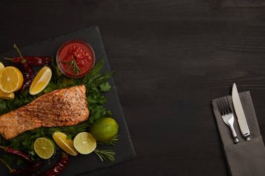 top view of grilled salmon steak, pieces of lime and lemon, sauce and cutlery on black surface