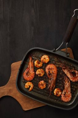 top view of grilled shrimps on wooden cutting board on black tabletop