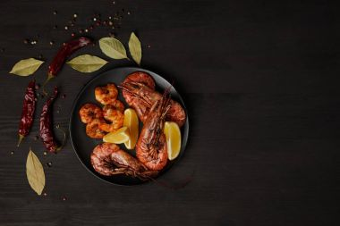 top view of grilled shrimps and lemon pieces on plate with arranged spices around on black surface