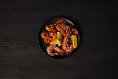 top view of grilled shrimps and lemon pieces on plate on black surface