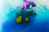 Fotografie Zblízka pohled míchání cákance modré, tyrkysové, žluté a fialové barvy ve vodě