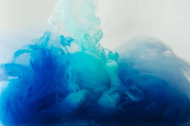 close up view of mixing of blue and turquoise paints splashes in water isolated on gray