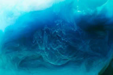 full frame image of mixing of blue, black, turquoise and white paints splashes in water