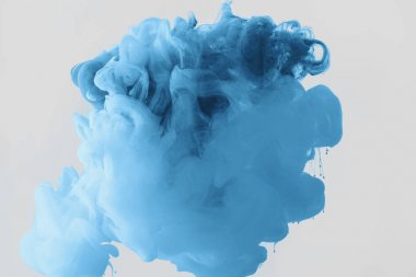 Close up view of mixing of bright pale blue and blue ink splashes in water isolated on gray