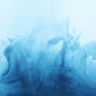 Full frame image of mixing of bright pale blue and blue ink splashes in water