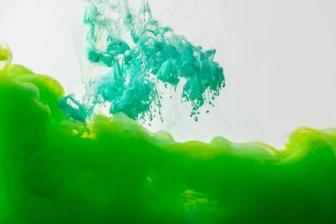 close up view of mixing of green and bright turquoise paints splashes in water isolated on gray