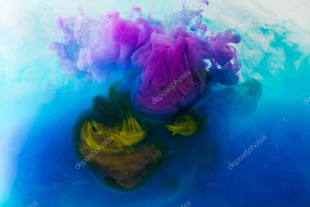 Full frame image of mixing of blue, turquoise, yellow and purple inks splashes in water