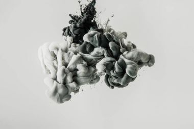 close up view of mixing of light gray and black paints splashes in water isolated on gray