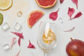 top view of arrangement of wineglass, exotic fruits, ice cubes and flower petals on white surface