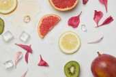 Fotografie top view of arrangement of fresh exotic fruits, ice cubes and flower petals on white surface