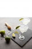 Fotografie Zblízka pohled margarita koktejl s kousky limetky a dřevěné ždímací na šedém povrchu na bílém