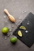 Photo flat lay with wooden squeezer, limes and ice cubes for cocktail on grey surface