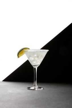 Close up view of tasty margarita cocktail with lime and ice on tabletop on black and white backdrop