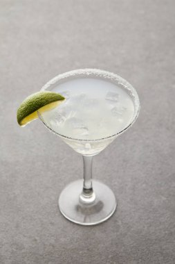 close up view of alcohol cocktail with lime piece and ice on grey surface