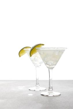 close up view of alcohol margarita cocktails with lime on grey surface on white