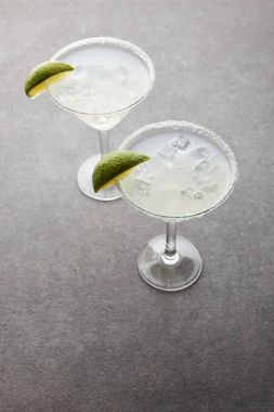 close up view of cold margarita cocktails with pieces of lime on grey tabletop