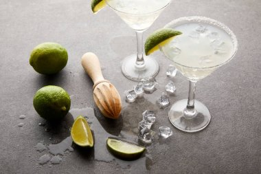 close up view of alcohol cocktails with pieces of lime, ice cubes and wooden squeezer on grey tabletop