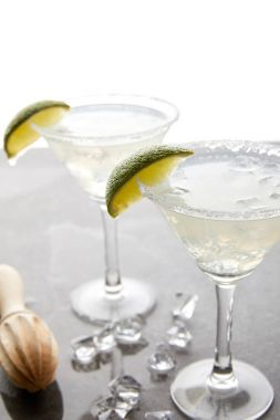 Selective focus of alcohol margarita cocktails with lime pieces and wooden squeezer on grey surface on white
