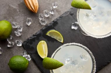 Top view of margarita cocktails with pieces of lime, ice cubes and wooden squeezer on grey tabletop stock vector