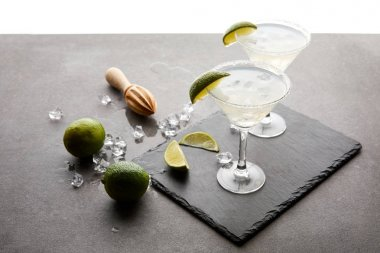 Close up view of alcohol cocktails with pieces of lime, ice cubes and wooden squeezer on grey tabletop stock vector