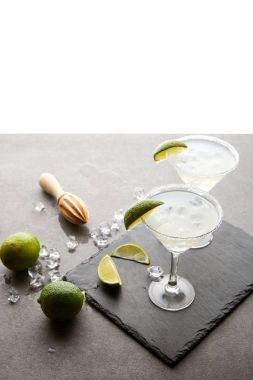 Close up view of margarita cocktails with lime pieces and wooden squeezer on grey surface  on white